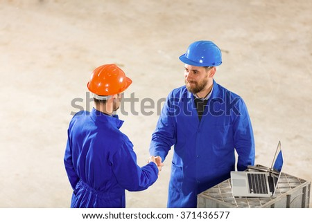 Two protective line worker handshake in factory. - stock photo