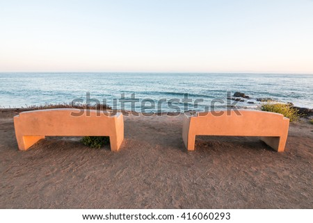 Two public benches overlooking the Pacific ocean at Carpinteria State Park, California. - stock photo
