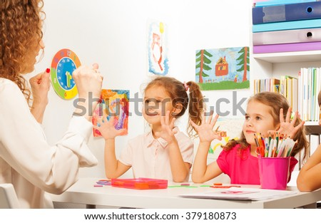 Two pupils doing finger exercises as their teacher - stock photo