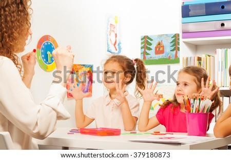 Two pupils doing finger exercises as their teacher - stock photo