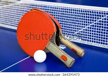 Two rackets for ping-pong on a blue table. - stock photo