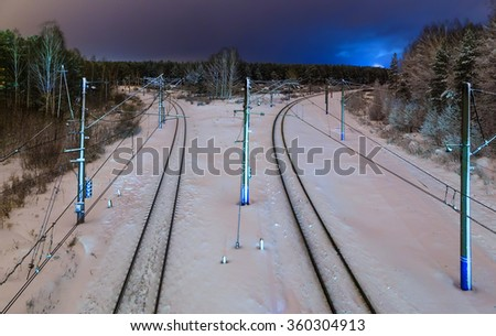 two railway road at night with city lights in the background - stock photo