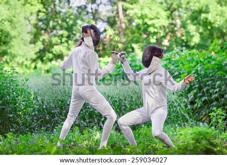 Two rapier fencer women fighting over beautiful nature park background - stock photo