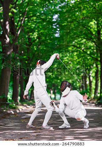 Two rapier fencers women fencing on park path - stock photo