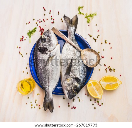 two raw dorado fish in blue plate with spoon,lemon,herb and spices, top view - stock photo