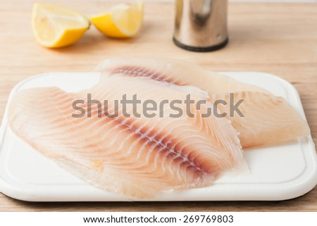 two raw fish fillets on white chopping board - stock photo