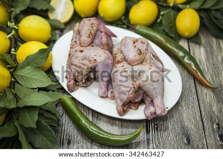Two raw fresh chicken on porcelain plate with lemon and chili  on the wooden background. - stock photo