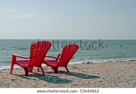 Two Red Adirondack Beach Chairs Sanibel Florida - stock photo