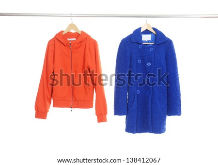 Two red and blue female dress ,coat isolated on hanging - stock photo