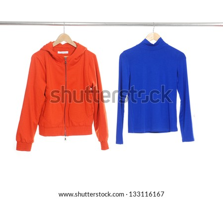 Two red and blue female dress isolated on hanging - stock photo