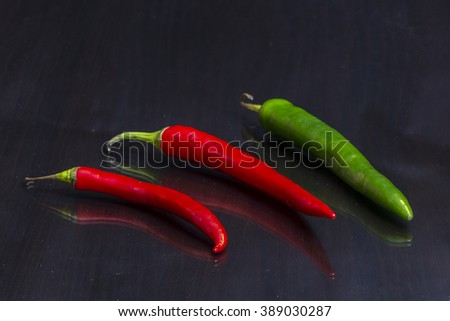 Two red and one green hot chili peppers are on a mirror black wooden table - stock photo