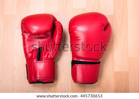 Two red boxing gloves on wooden table - stock photo