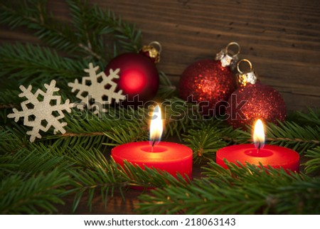 Two Red Candles Lighting a Christmas or Advent Decorated Background with Fir Tree Branches, Snowflakes and Christmas Balls - stock photo