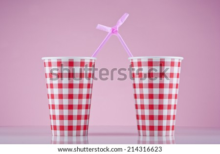 Two red checked cups and two purple straws bound together - stock photo