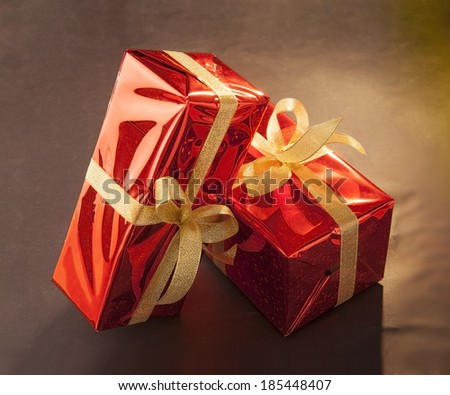 two red Christmas gift with halogen pattern with a bow on a black textured background - stock photo