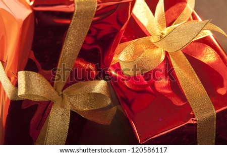 two red Christmas gifts with halogen pattern with a bow on a black background - stock photo