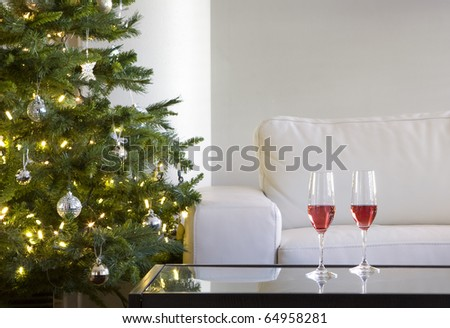 two red drinks by christmas tree in modern white living room - stock photo