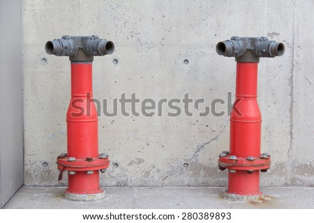 two red fire hydrant poles in front of the wall - stock photo
