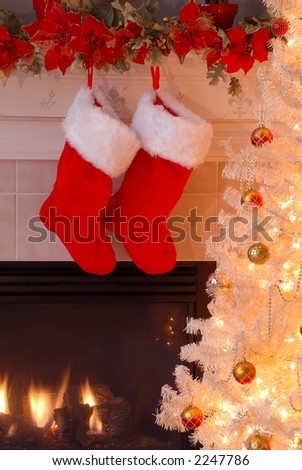 Two red fur stockings hang on the mantle over the fireplace as an antique lighted Christmas tree glows in the evening light. - stock photo