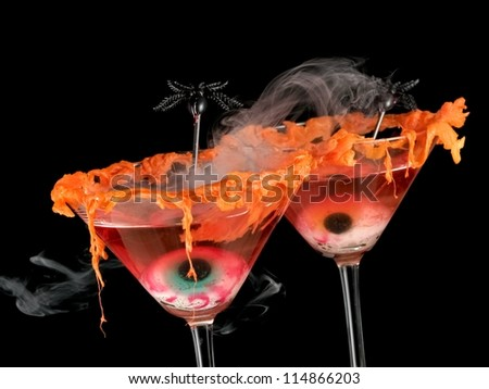 Two red halloween cocktails with eyes and smoke - stock photo