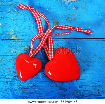 two red hearts on blue wooden background - stock photo