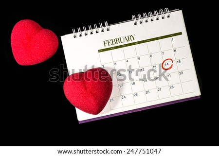 Two red hearts with calendar noted valentine's day on black background - stock photo