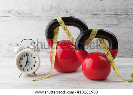 Two red kettlebells with measuring tape and vintage clock on rustic white wooden table. Health and fitness concept. - stock photo