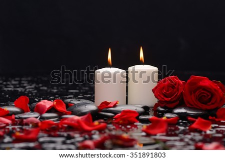 Two Red rose petals with white candle and therapy stones  - stock photo