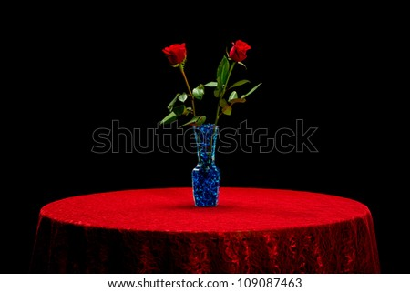 Two red roses in a vase with blue stones on a red lace tablecloth isolated on a black background. - stock photo