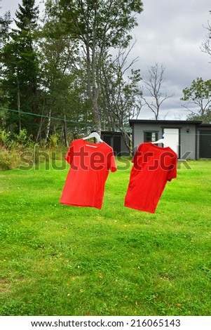 Two red shirts on clothesline in sunny day - stock photo