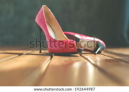 Two red stilettos over wooden planks floor - stock photo
