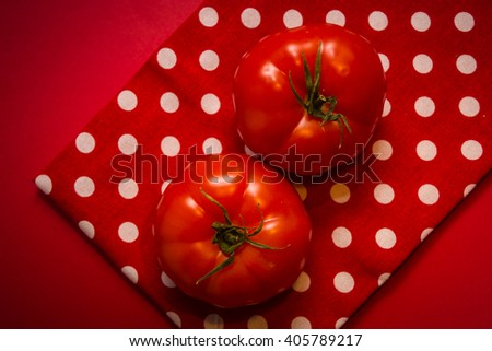 Two red tomatoes lying on the red tea-towel and red background - stock photo