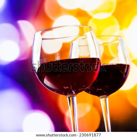 two red wine glasses against colorful bokeh lights background, festive and fun concept - stock photo