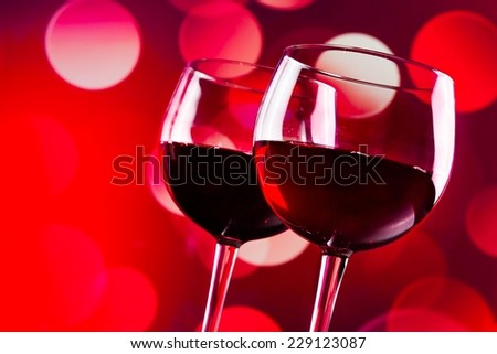 two red wine glasses against red bokeh lights background, festive and fun concept - stock photo