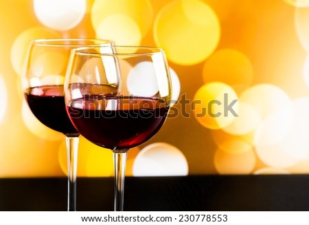 two red wine glasses on wood table against golden bokeh lights background, festive and fun concept - stock photo