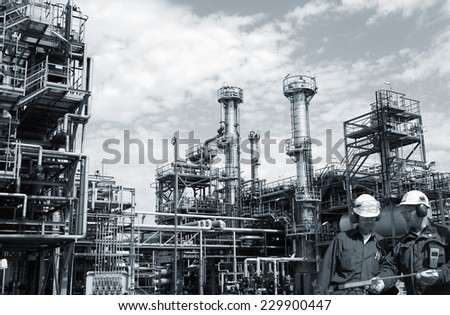 two refinery workers with large industrial refinery in background - stock photo