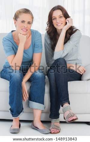 Two relaxed women posing while sitting on the couch and looking at camera - stock photo