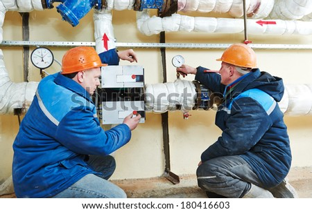 two repairman engineer of fire engineering system or heating system open the valve equipment in a boiler house - stock photo
