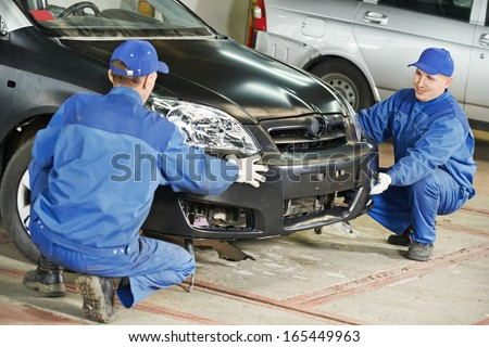 Two repairman mechanics matching automobile body bumper on damaged car at repair service station - stock photo