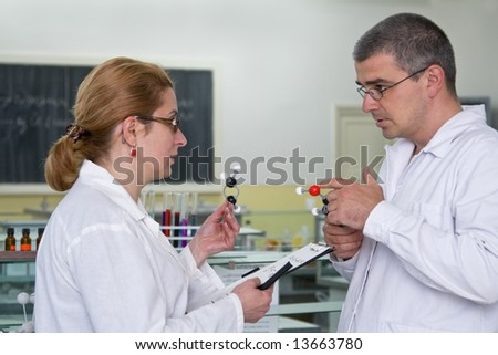 Two researchers discuss about the experiment strategy in a laboratory.All the inscriptions are mine. - stock photo