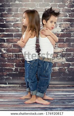 Two resentful kids in studio - stock photo