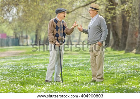 Two retired seniors having a conversation in a park on a sunny spring day  - stock photo