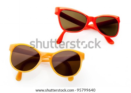 Two retro sunglasses from the eighties. Red and yellow frame. Vintage objects. - stock photo
