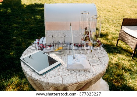 Two rich blank decorated wedding glasses with sprig of delicate beige roses on the table with tablet pc for congratulations - stock photo
