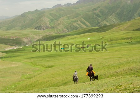 Two riders on horseback go away in the valley between the green mountains - stock photo