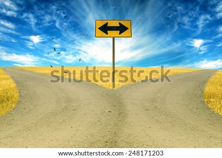 two roads, road sign ahead with arrows blue sky background. Countryside landscape  - stock photo