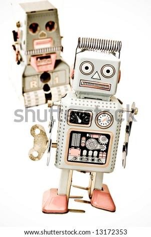 two  robot toys isolated on white ( retro inspired image  ) - stock photo