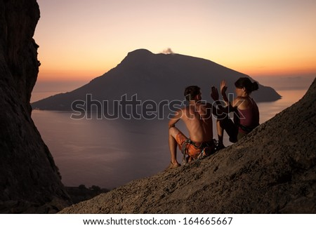 Two rock climbers having rest at sunset. Climbers giving high five and cheering. With picturesque view of Telendos Island in front. Kalymnos Island, Greece.  - stock photo