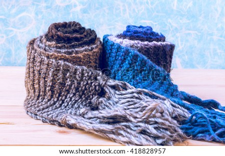 Two roll knitted scarf on wooden and paper background. - stock photo