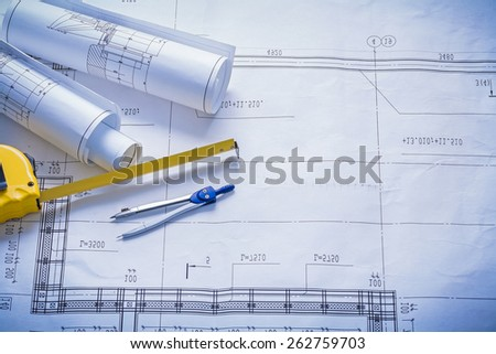 two rolled blueprints tapeline compass with copyspace construction concept  - stock photo